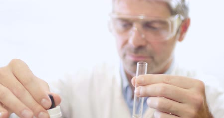 sertlik : Scientist in a lab putting some chemicals into a test tube due to test the hardness of the water... Stok Video