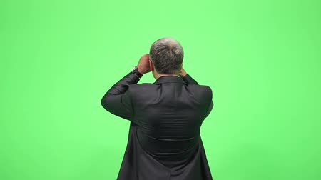 looking far away : Man in a suit looking at something in the distance making binocular with his hands,chroma key... Stock Footage
