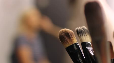 продукты : Some brushes in focus, make-up artist in the back preparing a woman by giving her a make up...