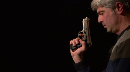 trigger : Man sitting in the dark,he has a gun,he is not sure what to do,he points the gun to camera...