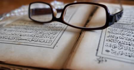 verse : Footage of a Quran lying on a table with reading glasses on it and a tasbeeh in the back... Stock Footage