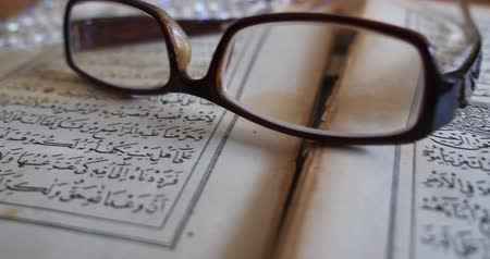 verse : Quran lying on a table with reading glasses on it and a tasbeeh in the back,moving shot...