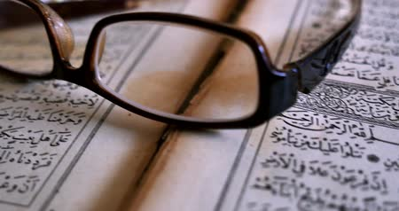 verse : A Quran lying on a table with reading glasses on it,a tasbeeh in the back,shot is moving...