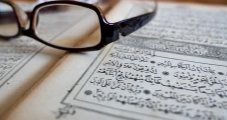 verse : Quran on a table,reading glasses on it and a tasbeeh in the back,shot is moving from right...