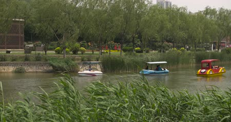gongyuan : 4K People ride in small boats on a lake in a green park area. Two shots combined in one clip.