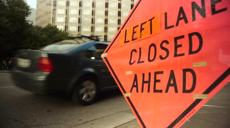 jel : Left lane closed construction warning sign with street in background.