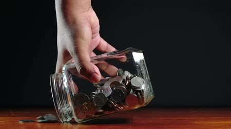 holding onto : Male hand pouring Malaysian coins onto the table but left some coins inside