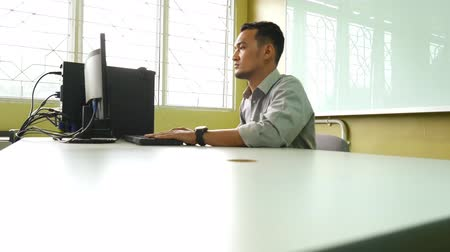 employee : A serious male employee using a computer and surfing the internet, camera moving from left to right