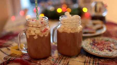 harmanlanmış : Two mugs with cocoa and marshmallows are on the Christmas table. Stok Video
