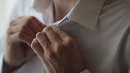 хронометр : Man buttoning a button on a white shirt