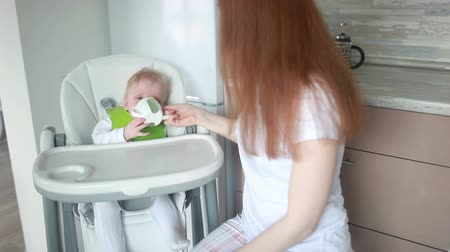 alcançando : Mom feeding baby cheese on a high chair from a spork utensil.