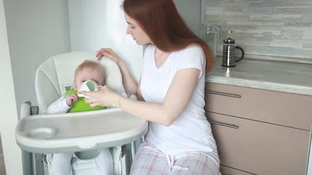 Mom feeding baby cheese on a high chair from a spork utensil.