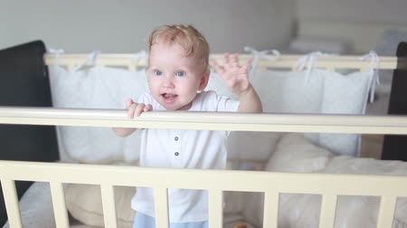 Cute laughing baby standing in a white round bed.