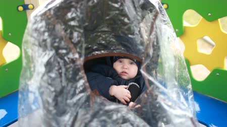 A child in a pram under a transparent cover. Wideo