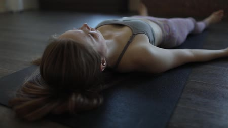 A young woman meditates in the position of Shavasana.
