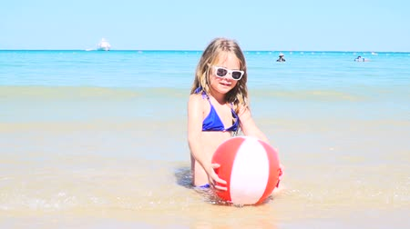 eye ball : Girl with blue bikini sitting in the sea and playing with water ball