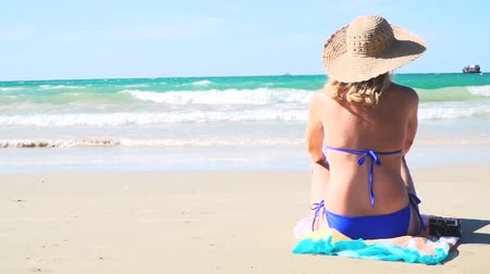 senhora : young blond woman with blue bikini and straw hat sitting on the beach and looks at the sea