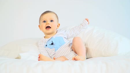 infante : Baby with big blue eyes and blond hair in bed Stock Footage
