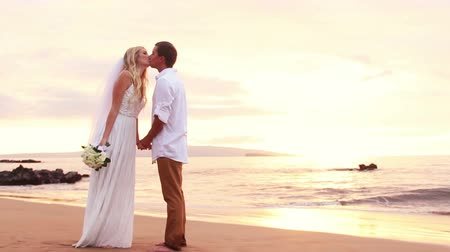 Just married couple on beach at sunset