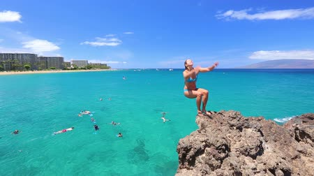 woman jumping from cliff into the ocean doing backflip
