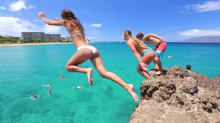 jump : friends jumping from cliff into the ocean Stock Footage