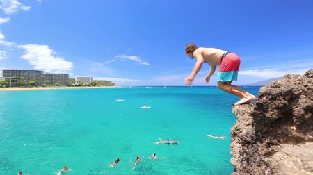 man jumping from cliff into the ocean