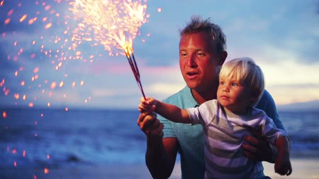Father and son lighting sparklers on the beach at sunset Wideo