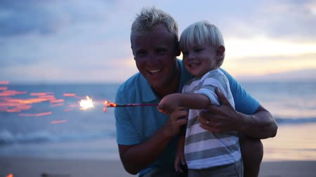 Father and son lighting sparklers on the beach at sunset Vídeos