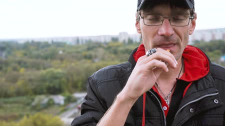 addiktív : A man smokes a cigarette. Guy with glasses smokes cigarettes. Tobacco smoke