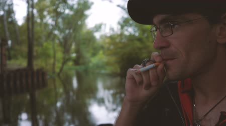 zapalovač : A man smokes a cigarette. Guy with glasses smokes cigarettes. Tobacco smoke