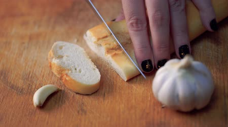 bagietka : Slicing baguette on chopping board, slow, super slow. Cutting white bread. Slicing baguette on table. Baguette traditional french bread on the table cutting close-up. Wideo