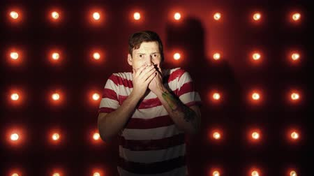szál : The man on the red background is shocked or horrified by what he saw , many light bulbs background above the red wall. shine. scene. Emotional man, the lights in the background Stock mozgókép