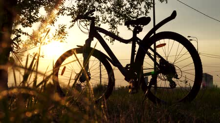 životní styl : Beautiful close up scene of bicycle at sunset, sun on blue sky with vintage colors, silhouette of bike forward to sun.