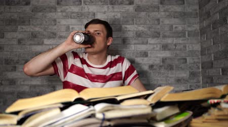 akademický : Young man drinking energy drink while studying. College student concept. Energizing before learning