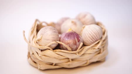 natural spicy : Garlic in a wicker basket, on a white background. Dried French garlic. Red garlic. Stock Footage