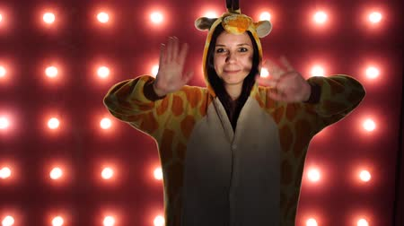 pizsama : pajamas in the form of a giraffe. emotional portrait of a woman on an orange background. crazy and funny female in a suit. animator for childrens parties