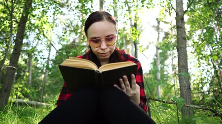 field study : Woman reading a book in a green summer forest.