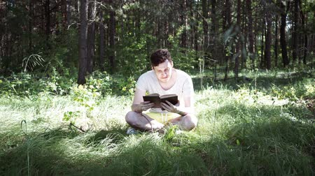 field study : Young handsome man reading book in open space Stock Footage