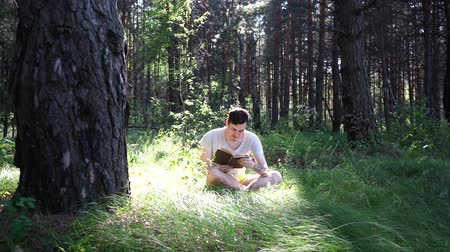 field study : Man reading a book in a green summer forest.