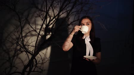 pauza : Woman with cup of coffee in dark place. Young dreamy woman enjoying coffee while standing in ray of light beside branches of tree in darkness
