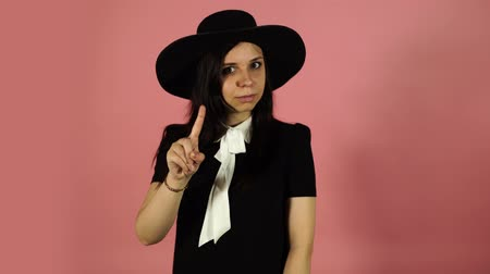 sem camisa : Young female in black dress and hat. Attractive woman wearing black outfit standing on pink background and pointing to side with one finger