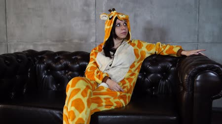 piada : Woman in costume of giraffe sitting on couch. Smiling young woman in funny pyjamas of giraffe sitting on leather couch and looking at camera