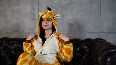 éretlen : Woman in costume of giraffe sitting on couch. Smiling young woman in funny pyjamas of giraffe sitting on leather couch and looking at camera