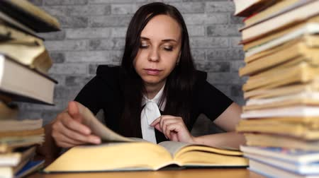 задумчивый : Tired female student reading among books. Pensive young woman sitting at table with pile of book and reading on background of grey wall