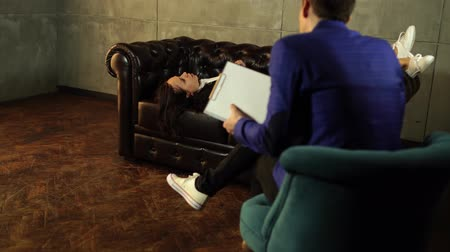sorguya çekme : Young woman answering questions of faceless man. Young confused woman sitting on leather couch and talking with unrecognizable confident man in suit