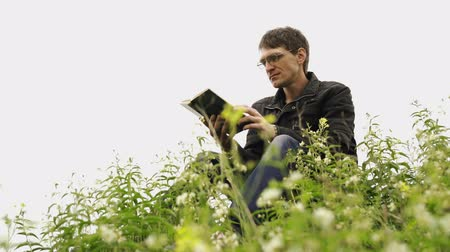 field study : Man reading book in green hilly field. Side view of young handsome man in glasses and warm jacket reading book in open space on background of green hills Stock Footage