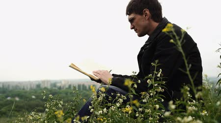 мудрость : Man reading book in green hilly field. Side view of young handsome man in glasses and warm jacket reading book in open space on background of green hills Стоковые видеозаписи