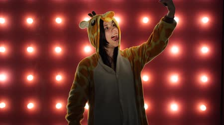 éretlen : Woman in costume of giraffe on red background with light bulbs. Female taking a selfie Stock mozgókép