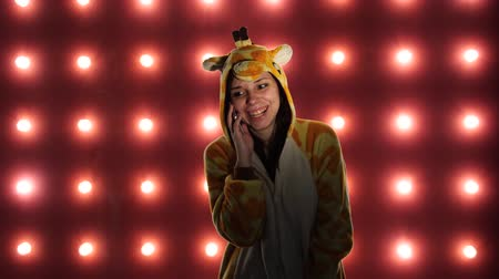 dětinský : Female calling on the phone. Woman in costume of giraffe on red background with light bulbs.