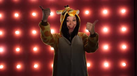 éretlen : Female doing like a like with thumbs up on a red background. Woman in a bright childrens pajamas in the form of a kangaroo. costume presentation of childrens animator.